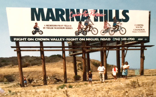 Dave Marriner and family under the Marina Hills billboard that features them, 1990
